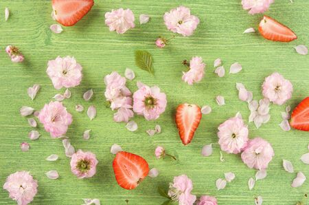 Colorful summer or spring nature background. Pink almond flowers, bud, leaf and petal on green wooden natural background, flat lay. Top view Stockfoto