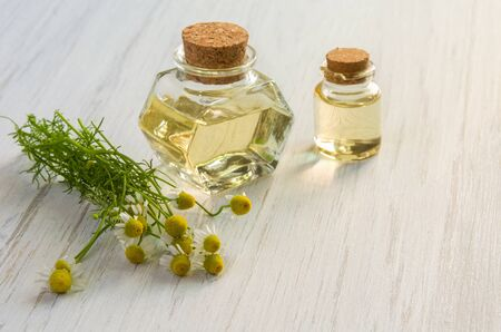 Chamomile flower water or oil in glass bottle on wooden table background. Aromatherapy, cosmetics or SPA concept