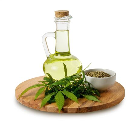 Hemp oil with green leaves and seeds in glass jar on wooden cutting Board isolated on white background