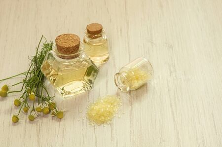 Chamomile water hydrolate in glass bottles, yellow bath salt and fresh flowers on white wooden table background