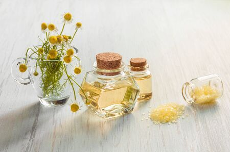 Pharmacy yellow chamomile flower and medicinal infusion in glass bottles and Spa salt on wooden light background