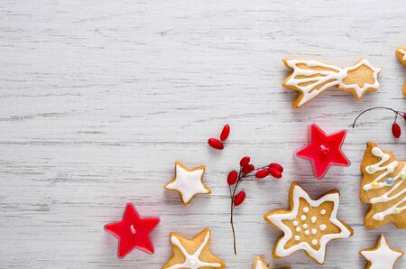 Homemade Christmas cookies with white icing, red candles and berries on wooden background with copy space