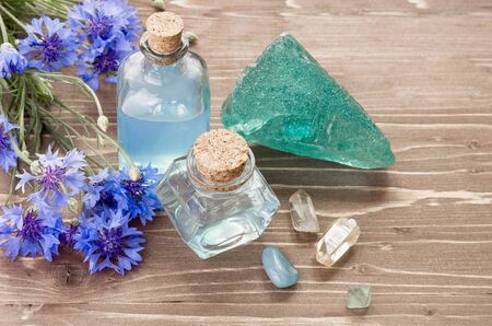 Aromatherapy or cosmetic concept. Cornflower flower, water in glass bottle and natural minerals stones on wooden brown background