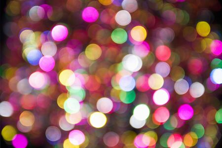 Pink, yellow and blue blurred festive bokeh. Christmas bright light holiday background.