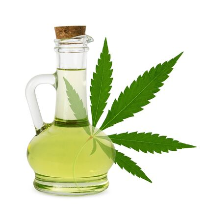 Hemp oil isolated. Sativa plant seed oil in glass bottle and fresh green cannabis leaf on white background