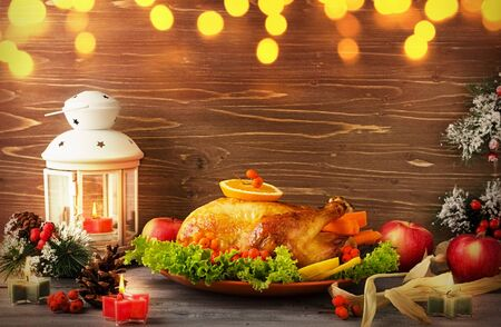 Christmas traditional Turkey on a platter with berries and vegetables on a wooden table background with flashlight Stock Photo
