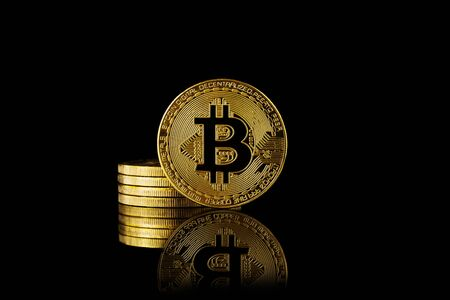 Bitcoin coins are a stack. Black background with reflection