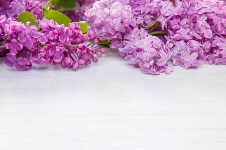 Spring lilac flowers as frame on white wooden table background, copy space