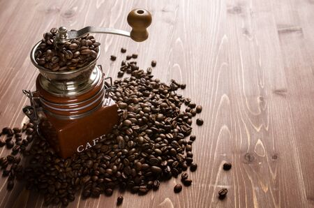 Handcrafted manual coffee grinder (mill) with coffee beans on brown wood background, back light, copy space Imagens