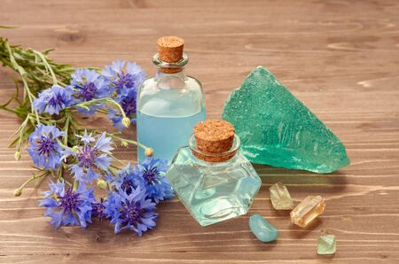 Cornflower flowers bouquet and blue essence water in bubbles on wooden background. Aromatherapy or SPA concept