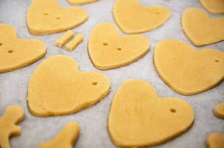 Cookies made from dough in the shape of heart lies on the baking sheet before baking
