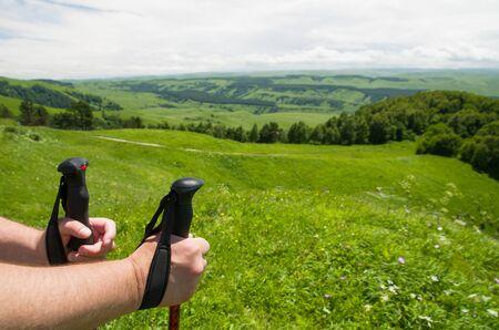 Nordic walking hiking concept - closeup of man's hand holding nordic walking poles. Beautiful mountain summer landscape, walking on mountain trails