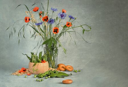 Still life with red poppies, cornflowers and green peas on grey blue background with copy space