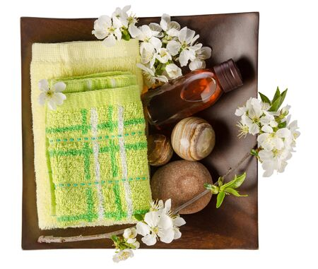 Towel, bath salt and essential oil with spring flowers in wooden bowl isolated on white Фото со стока