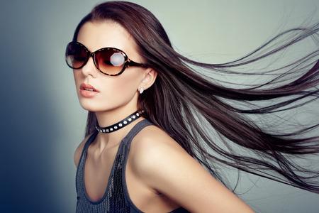 poses de modelos: Young beautiful girl in sunglasses. Pretty model poses at studio. Foto de archivo