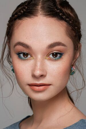 Beautiful woman face. Perfect makeup. Beauty. Cosmetic. Eyeshadow. Elegant hairstyle. Jewelry. 版權商用圖片