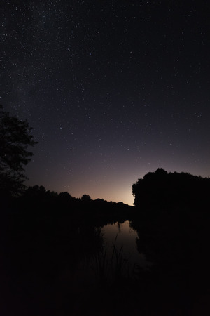 nebulae: Night sky with bright stars. Against the background of the pond surface. View constellations and nebulae.