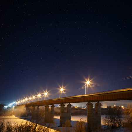 Highway bridge with a starry sky, lit by lanterns. Night landscape in the winter.