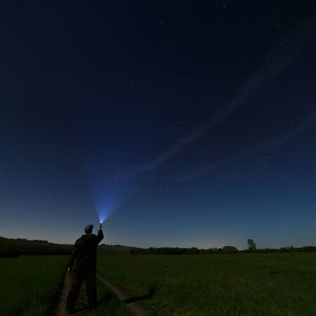 starry night: Man lantern illuminates the dark starry sky. Photographed by the moonlight.