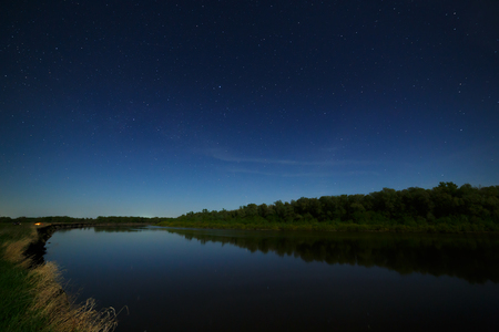 starry night: The stars in the night sky are reflected in the river. The landscape is photographed by moonlight. Stock Photo