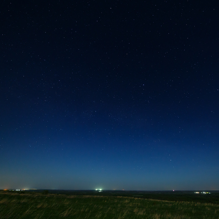 starry night: Stars in the night sky with city lights on the horizon. The landscape is photographed by moonlight.