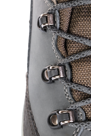 Fastening of laces on boots for mountain hikes with reinforced soles and membrane material. Stock Photo
