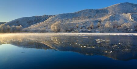 Freezing river from the hilly banks and large ice floes. A sunny day with a cloudless sky. Stock Photo