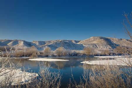 Freezing river from the hilly banks and large ice floes. A sunny day with a cloudless sky. Standard-Bild