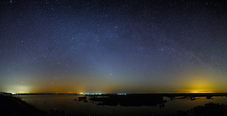 The stars of the Milky Way in the sky before dawn. Night landscape with a lake. Panoramic view of the starry space.
