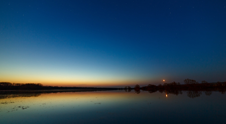 Sky with the stars before dawn. Night landscape with a lake.