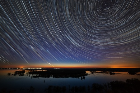 Star trails in the night sky. A view of the starry space in the background of the river. Stock Photo