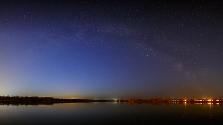 Stars of the Milky Way in the sky before dawn. Night landscape with a lake. Panoramic view of the starry space.