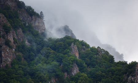 Clouds over the tops of the rocky mountains overgrown with trees. Photographed in the Caucasus, Russia.