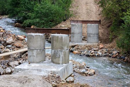 Construction of a bridge over a mountain river.