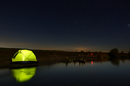Night sky with stars over the tourist tent by the river. The landscape was photographed on a long exposure.