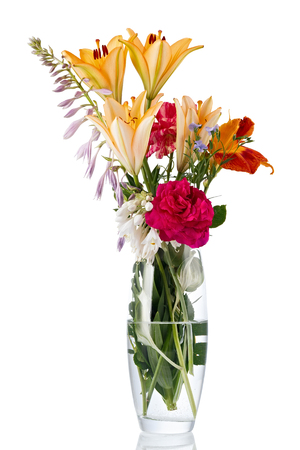 Blooming bouquet of flowers in a transparent vase with water. Isolated on white background.