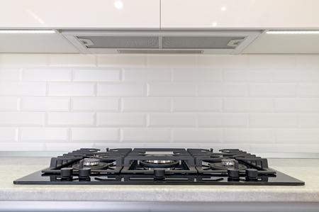 Cocina a gas y campana extractora en la cocina.