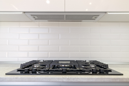 Gas stove and exhaust hood in the kitchen. Archivio Fotografico
