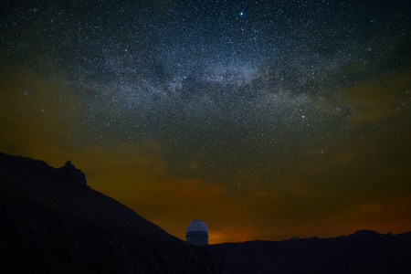 Observation at night the starry sky. Observatory for space exploration on the background of the bright Milky Way.