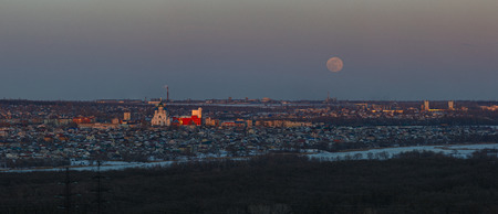 Full moon rising over the city. Sunset time in the twilight sky. Panoramic view of the Orthodox Church.