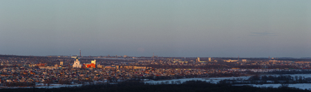 Evening lighting over the city. Sunset time in the twilight sky. Panoramic top view of residential district. Stock Photo