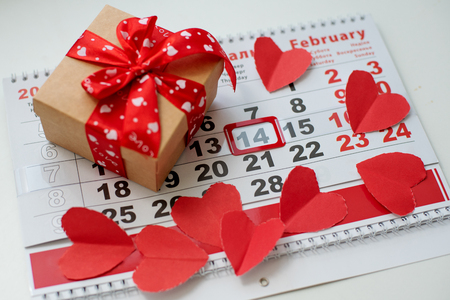 Calendar to Valentines day on the table with paper hearts