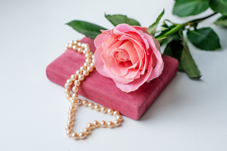 Pearl necklace on rose velvet box and pink one rose. Light background. Clouse-up. Stok Fotoğraf