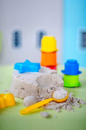 kinetic sand with toys on the green table in the children's room