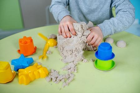 Un garçon adorable joue au sable cinétique à la maison Banque d'images