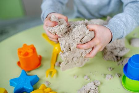 Un garçon adorable joue au sable cinétique à la maison