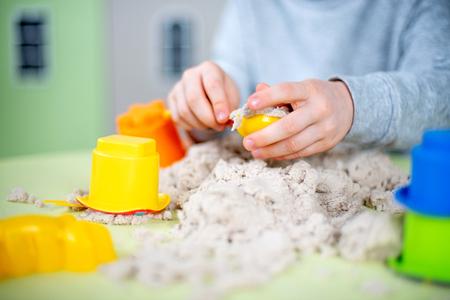 Adorable boy plays kinetic sand at home