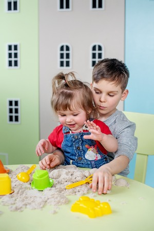 Adorable boy with little sister plays kinetic sand at home