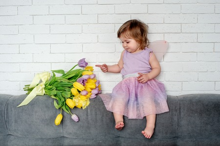Cute little girl with tulips in fairy clothes sits on a bed. Spring mood