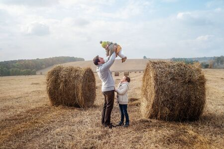 a yang boy and a little girl near a haystack in a field at sun day on autumn next to a tractor cleans field 스톡 콘텐츠